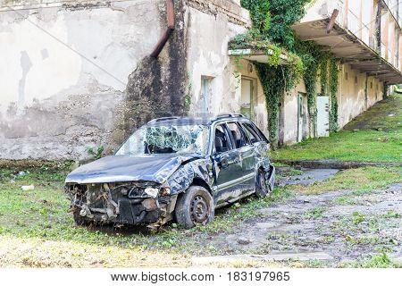 Broken car near an abandoned building in Abkhazia