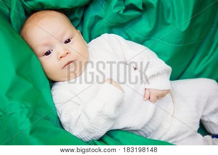 A small boy in a knitted white jacket is lying on a soft padded stool of green color. The child is resting and watching a six-month-old baby.