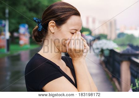 The woman holds her nose and cries. A frustrated brunette girl stands outside in the park and is sad.