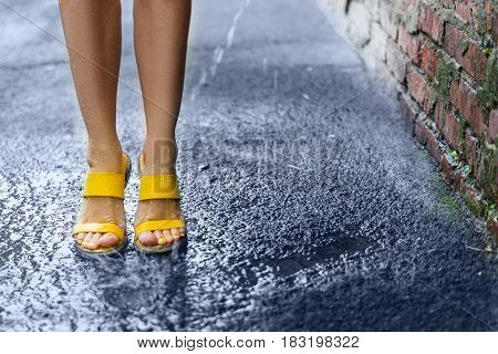Female feet standing in the rain on wet pavement near a brick wall. Yellow sandals on the feet of a young girl. Water splashes and drops on his feet.