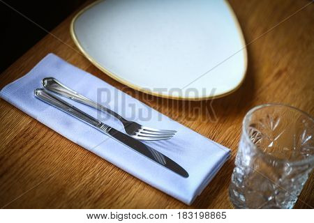 Close up shot of a fork and knife on a wooden table on a napkin near an empty plate and a glass.