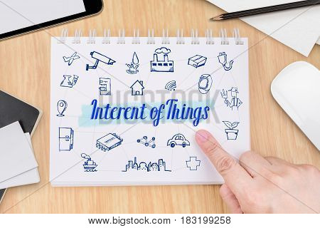 Hand Pointing At Internet Of Things (iot) On Book With Hand Drawn Feature Icon On Wood Table With Ta