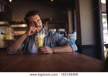 Thoughtful man having milkshake in restaurant