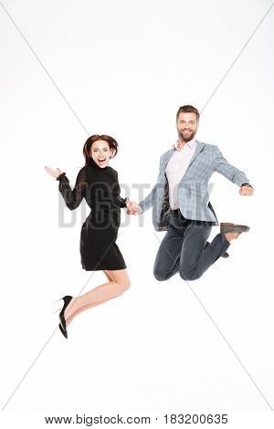 Image of happy young loving couple jumping isolated over white background. Looking at camera.