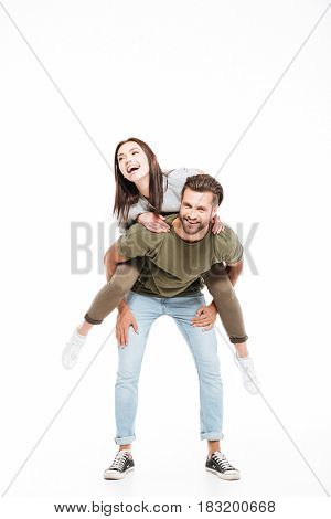 Cheerful woman sitting on back of her strong man isolated