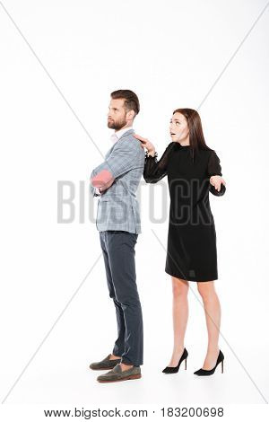 Picture of offended young loving couple swear isolated over white background. Looking aside. Woman ask for apologize.