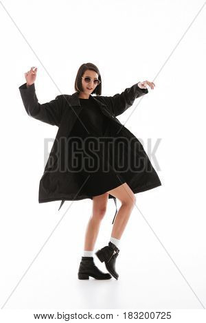 Photo of pretty young lady wearing sunglasses posing isolated over white background. Looking at camera.
