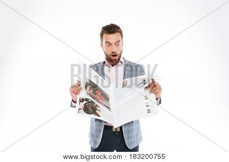 Photo of shocked young man standing isolated over white background and reading gazette. Looking aside.