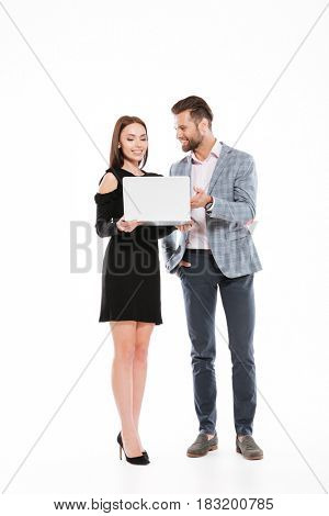 Picture of cheerful young loving couple standing isolated over white background. Looking aside while using laptop computer.