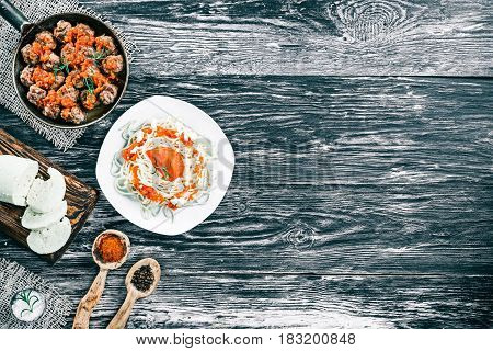 Plate of spaghetti and fried meatballs on frying pan on black and white wood background with fresh tomatoes, homemade cheese and spices