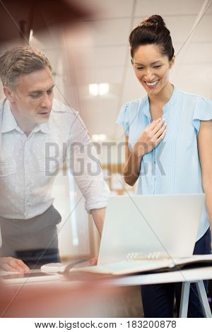 Businessman discussing with happy female colleague at office seen through glass