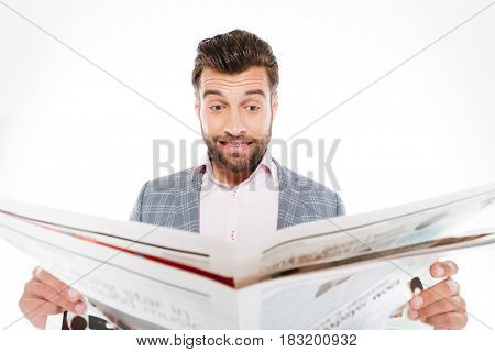 Image of confused young man standing isolated over white background while reading gazette. Looking aside.