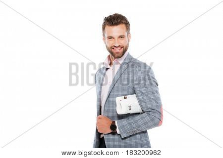 Image of happy young man standing isolated over white background and holding gazette. Looking at camera.