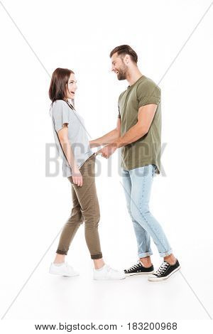Picture of smiling young loving couple standing isolated over white background. Looking aside.