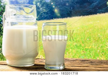 Fresh milk in a glass jug and a glass on a wooden vintage table against a sunny meadow