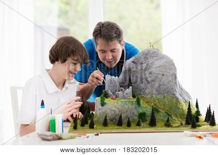 Father And Son Work On Model Building Project