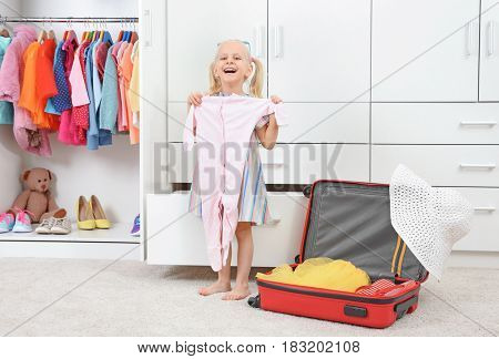 Cute small girl with clothes in wardrobe