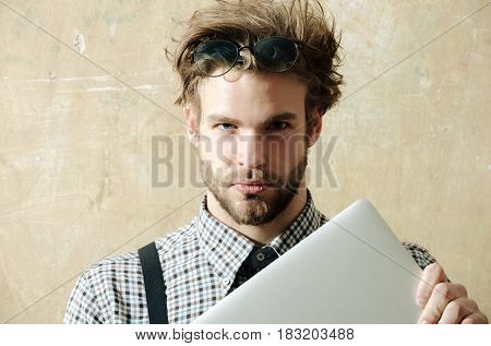 Education and technology. Handsome man or smart male student businessman with beard in nerd glasses on head with stylish blond hair and checkered shirt with suspenders holding laptop computer