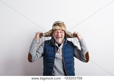 Handsome senior man in gray sweater, blue vest jacket and fur hat, smiling. Studio shot against white wall.