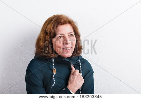Beautiful senior woman in green jacket, smiling. Studio shot against white wall.