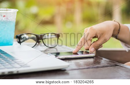 Close up woman hand use cell phone with laptop in coffee shop.
