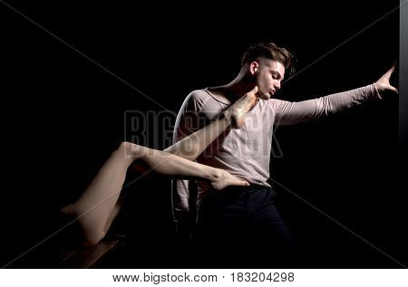 Handsome man or young caucasian macho with stylish haircut hair in grey tshirt with long sleeves casual wear posing with sexy female legs on back on black background