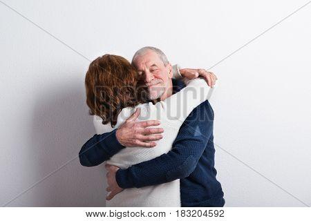 Beautiful senior couple in love hugging. Studio shot against white wall.