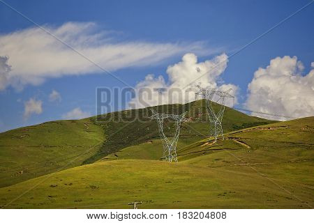 Lines Of Power Lines On Green Hills