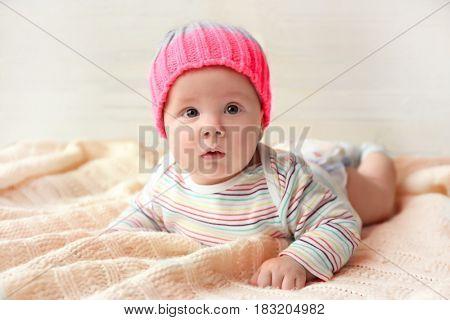 Cute little baby in hat lying on soft blanket
