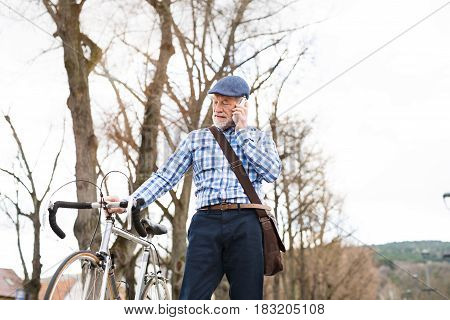 Handsome senior man in blue checked shirt with bicycle in town holding smart phone, making phone call. Sunny spring day.