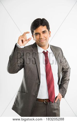 young indian businessman showing small quantity sign or posing like holding something in right hand in front of his face and camera, isolated over white background