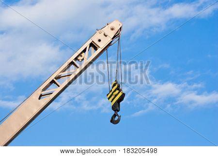 Small crane boom against blue sky .