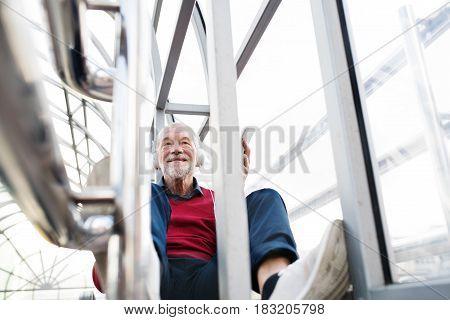 Handsome senior man holding smart phone, headphones on his ears, listening music, sitting in glass passage.