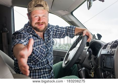 Bearded driver in a car cabin inviting to a journey
