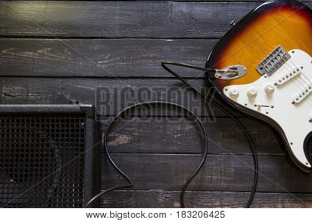 Electric Guitar With Amplifier Connected By Cable On Wooden Background