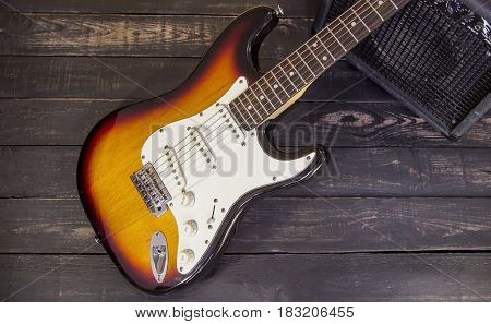 Electric Guitar With Amplifier On A Dark  Wooden Floor