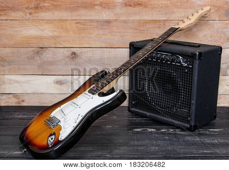 Electric Guitar With Amplifier On Wooden Background
