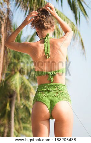 Sexy Tan Girl In Sunglasses Near The Palm Tree On The Beach In A Green Knitted Swimsuit, Back To The