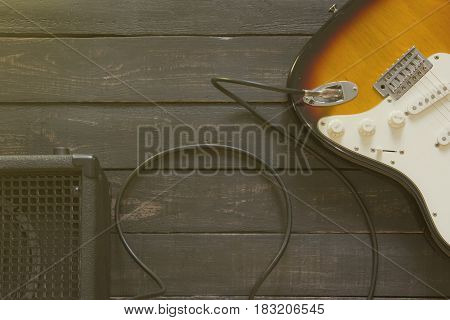 Electric Guitar With Black Amplifier Connected By Cable On Wooden Floor