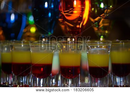 Glasses with colorful cocktails and layered shots mixed alcoholic drinks served in rows on countertop in bar or night club on blurred background. Entertainment and lifestyle