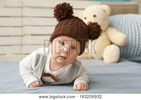 Cute little baby in funny hat lying on soft blanket