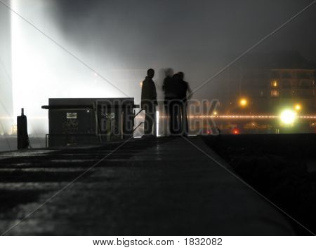 Jet D'Eau Lake Geneva Switzerland At Night with silhouette of people in the foreground poster