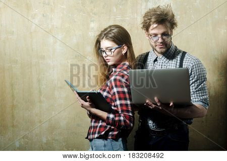 business and communication stylish fashionable nerd couple of students in geek glasses. Pretty girl or woman with notebook and handsome man with computer in checkered shirts on beige background