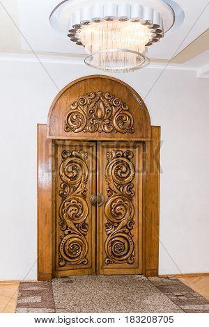 Beautiful carved wooden brown antique door. Indoor