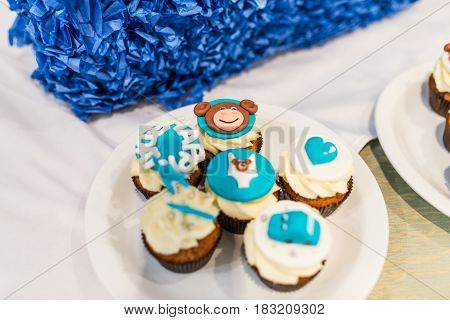 Focus on the white and blue cupcake with bear face for children's birthday