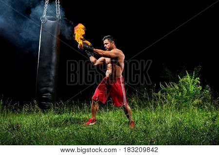 Sport motivation achievement concept. Professional male boxer training on a punching bag outdoors at night wearing burning boxing gloves. Professional martial arts fighter working out on punching bag