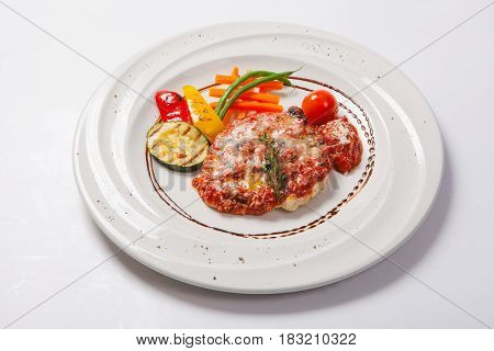 Grilled Chicken Breasts Coated With Melted Cheese, Vegetables And Tomato Sauce On A White Plate