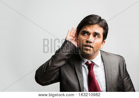 Young indian business man hearing something over white background