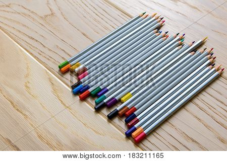 Various multicolored pencils are on wooden surface close to each other. Top view. Close up