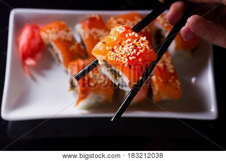 Japanese sushi rolls dish with hand holding one pice in chopsticks